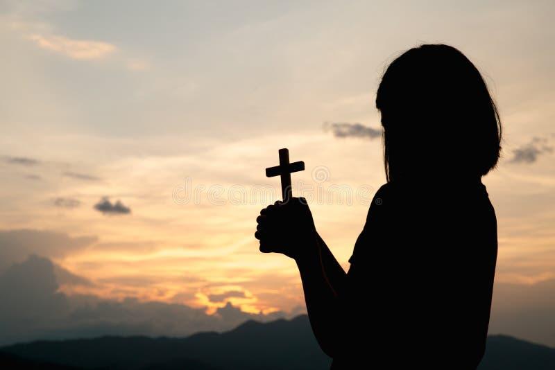 Kontur av en ung flicka som rymmer ett kors till gudmorgonen med härlig soluppgång, symbol av tro Kristen livbönkris royaltyfria foton