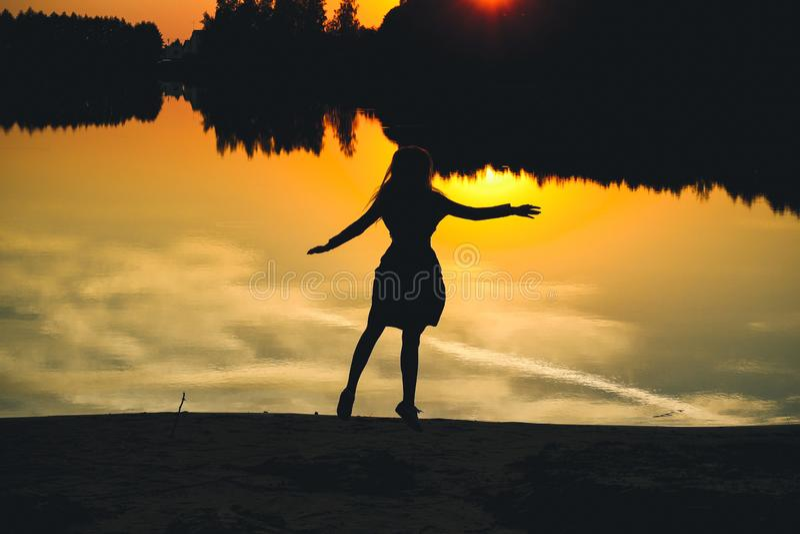 Kontur av en ung härlig flicka i ett hopp på en bakgrund av en solnedgång i reflexionsdammet royaltyfri bild