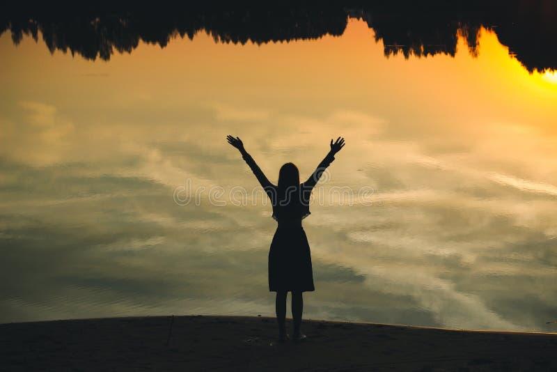 Kontur av en ung härlig flicka med händer upp mot bakgrunden av solnedgången i reflexionen av dammet arkivfoto