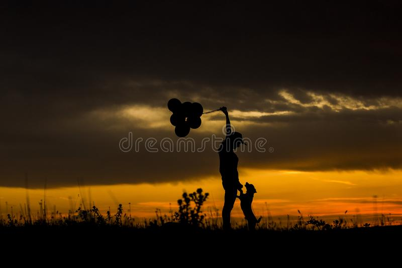 Kontur av en ung kvinna och hennes hund på solnedgången utomhus Hon är innehavballonger Älska för djurbegrepp royaltyfri foto