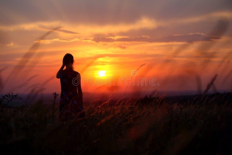 Kontur av en ung kvinna som bara står under solnedgång arkivbild
