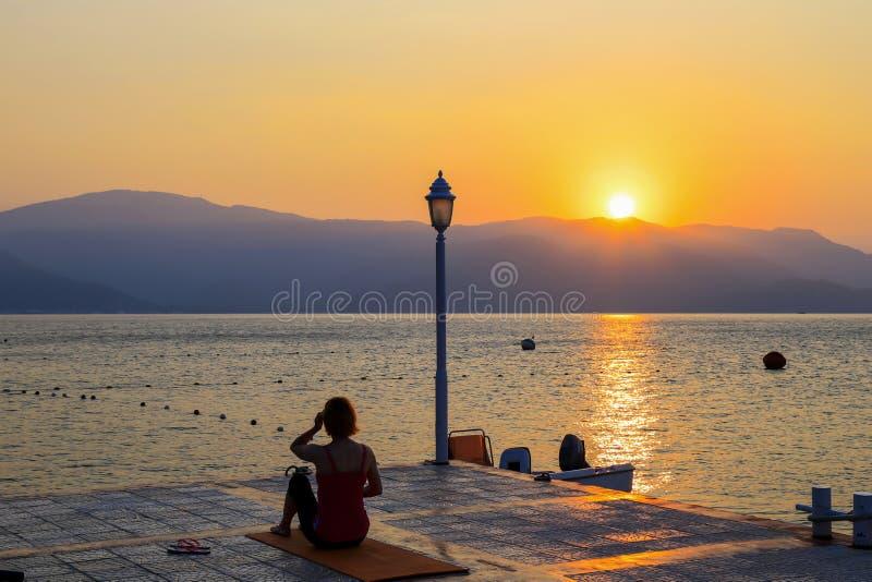 Kontur av en ung kvinna som utför yogaövningar på en sommarmorgon på kusten på soluppgång Sportar livsstil arkivfoton