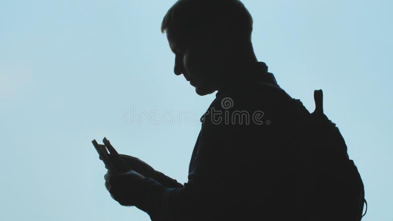 Kontur av en ung man som räknar dollar mot blå himmel royaltyfri foto