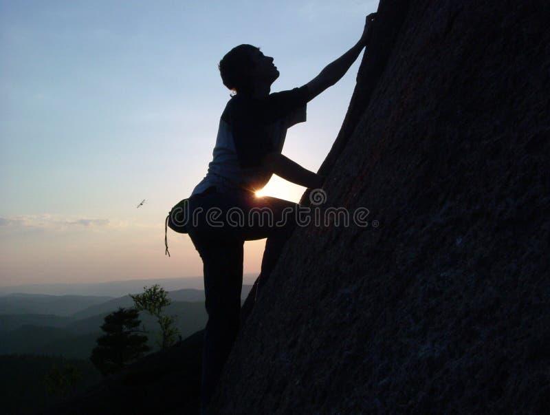 Kontur av en ung manlig klättrare som klättrar till överkanten av klippan på solnedgången utan försäkring arkivbilder