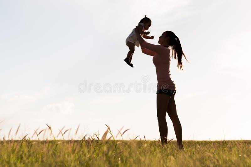 Kontur av en ung moder som rymmer lyckligt hennes barn upp i luften på ett gräs- fält royaltyfri fotografi