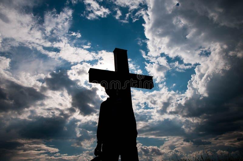 Kontur av en ung pojke och ett katolskt kors royaltyfri foto