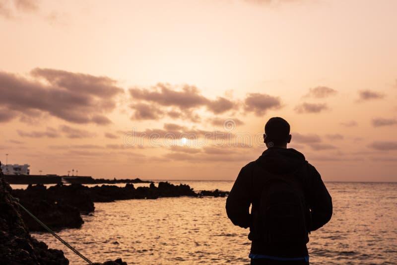 Kontur av en ung pojke på solnedgången som ser solen i Lanzarote, kanariefågelöar royaltyfria foton