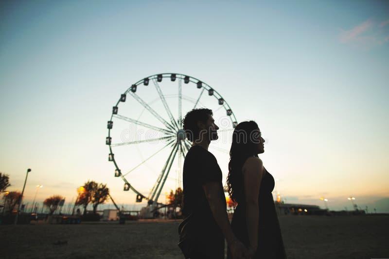 Kontur av ett älska par i aftonen Bak dem är hjulet av kontroll fotografering för bildbyråer