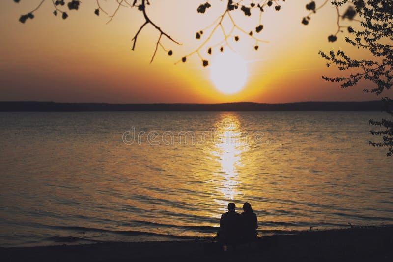 Kontur av ett förälskat sammanträde för par på en bänk på stranden och krama royaltyfria foton