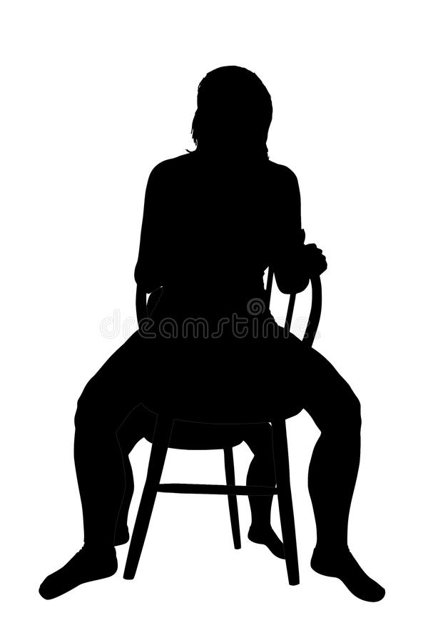 Kontur av ett kvinnasammanträde på en stol arkivbild