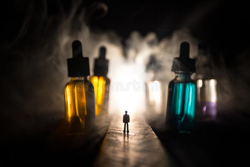 Kontur av ett mananseende i mitt av vägen på en dimmig natt med jätte- glasflaskor som fylls med den elektroniska cigaretten royaltyfri foto