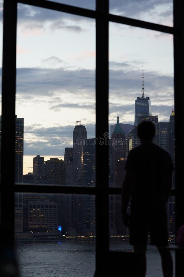 Kontur av ett manligt anseende av fönstret som ser den Manhattan horisonten, NY arkivbild