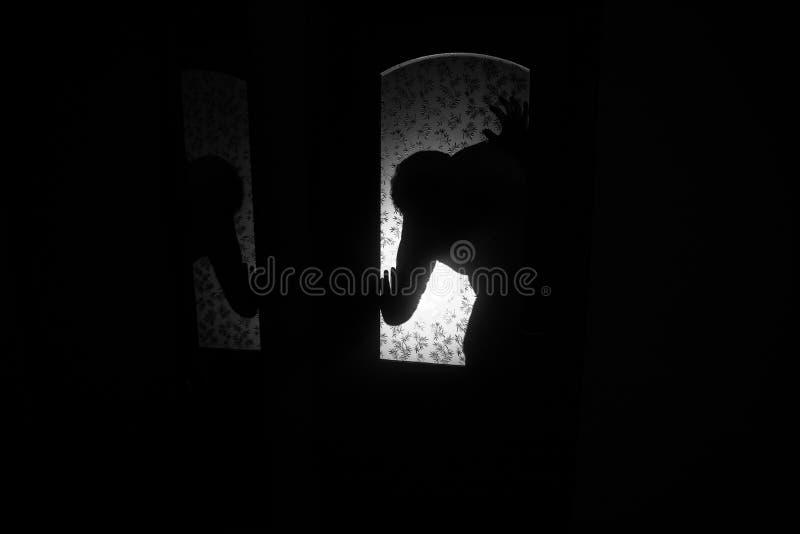Kontur av ett okänt skuggadiagram på en dörr till och med en stängd glass dörr Konturn av en människa framme av ett fönster på royaltyfri fotografi