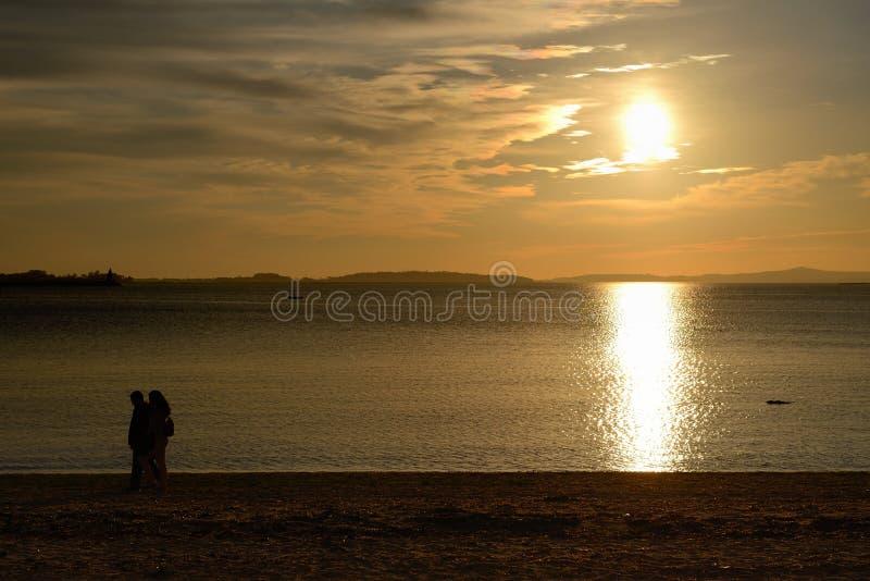 Kontur av ett par på stranden på solnedgångbakgrund arkivbild