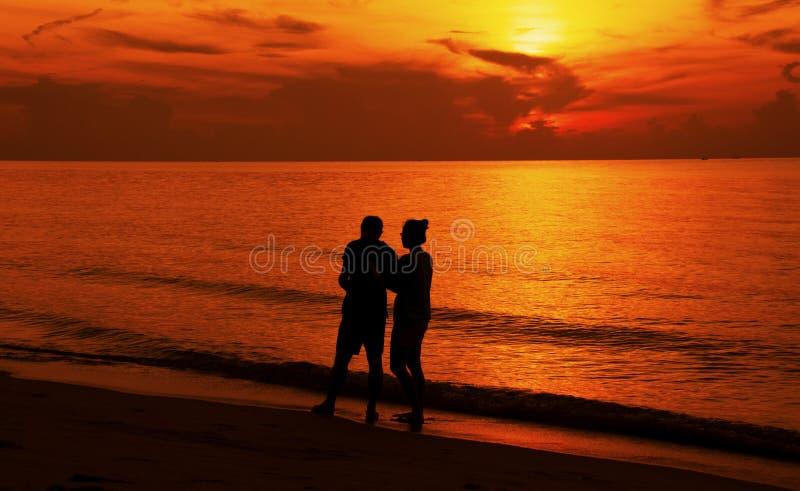 Kontur av ett par som går på stranden på solnedgången royaltyfri bild