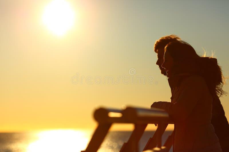 Kontur av ett par som ser horisonten på solnedgången royaltyfria bilder