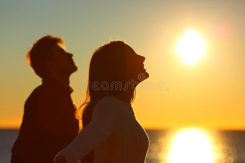 Kontur av ett par av vänner som andas på solnedgången arkivfoto