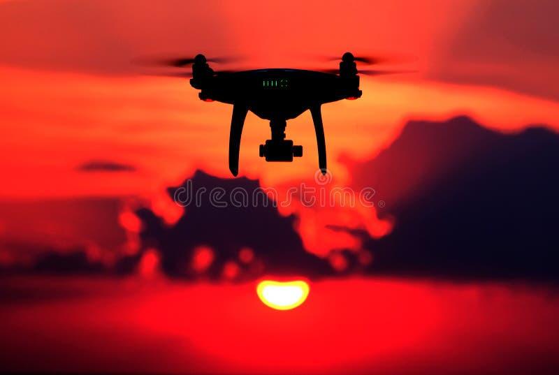 Kontur av ettkontrollerat surr mot en röd himmel Ett obemannat flyg- medel på solnedgången Begreppet av digitalization och royaltyfri bild