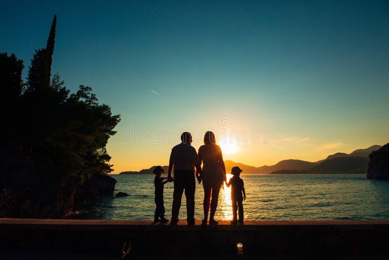 Kontur av föräldrar och två barn på havet på solnedgången Montene fotografering för bildbyråer
