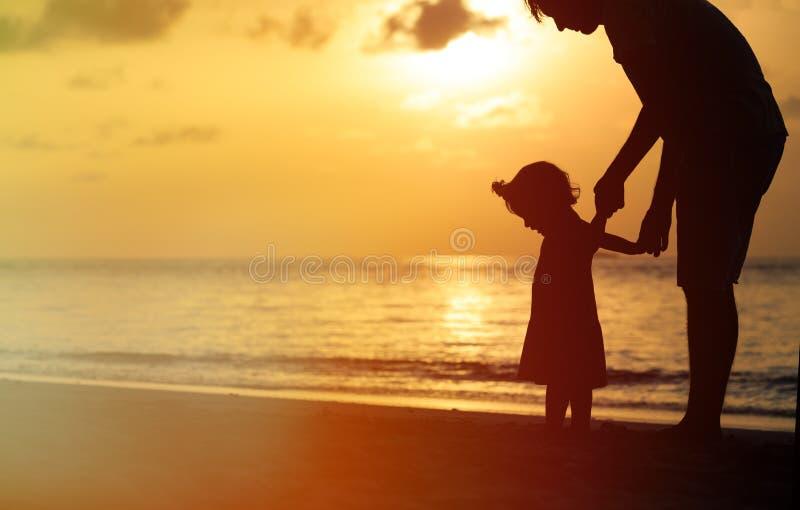 Kontur av fadern och den lilla dottern på solnedgången arkivfoto