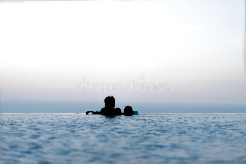 Kontur av farsan och ungar i simbassängen för att koppla av lycklig tid f?r familj royaltyfri fotografi