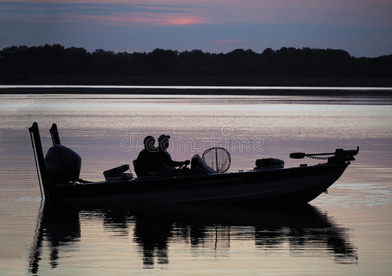 Kontur av fiskare i fartyg på soluppgång fotografering för bildbyråer