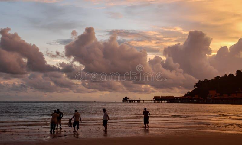 Kontur av fiskare med fisknät på en härlig strand i Langkawi, Malaysia på den orange solnedgången royaltyfri bild