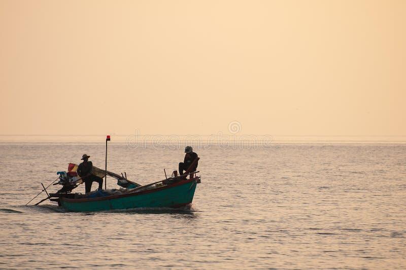 Kontur av fiskare med gul och orange bakgrund royaltyfri bild