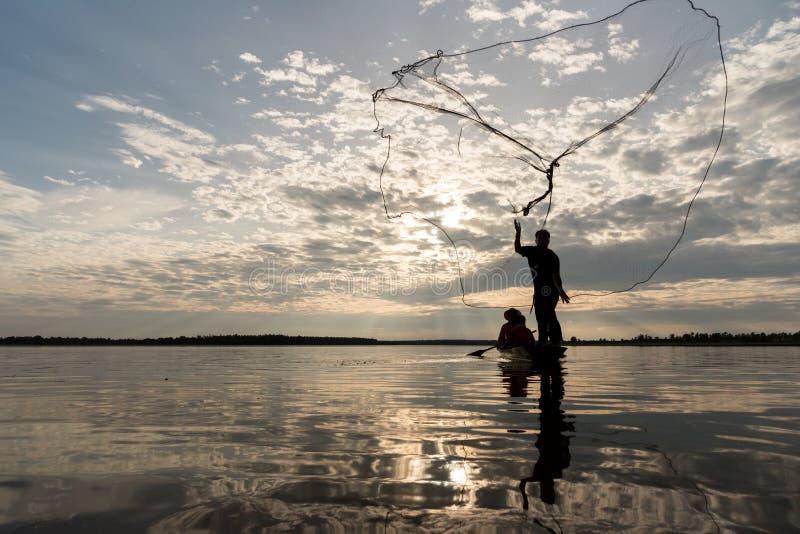 Kontur av fiskare som kastar netto fiske i solnedgångtid på W royaltyfria foton