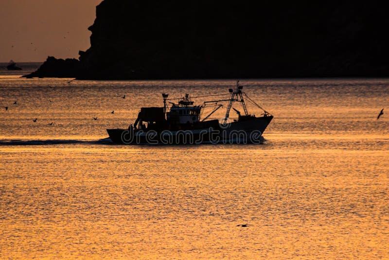 Kontur av fiskarefartyget på medelhavet under soluppgång i guld- solstrålar i MDiq, Marocko royaltyfri foto