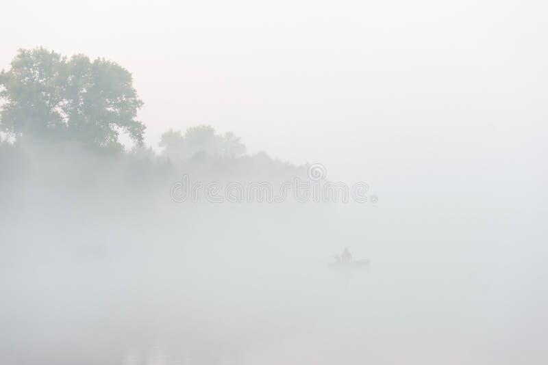 Kontur av fiskaren på en flod på den dimmiga morgonen arkivbild