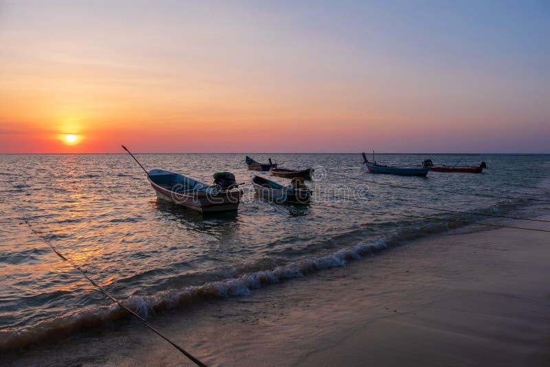 Kontur av fiskebåten på den tropiska stranden på solnedgången royaltyfri fotografi