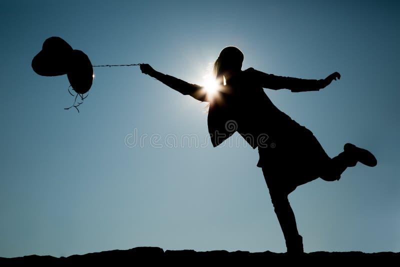 Kontur av flickan med ballonger på en rad arkivbild