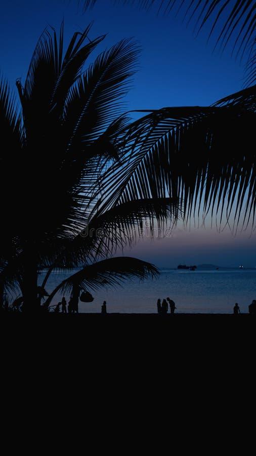 Kontur av folk på den tropiska stranden på solnedgången - turister som tycker om tid arkivbilder