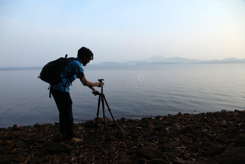 Kontur av fotografen med tripoden Ung man som tar fotoet med hans kamera i morgonen nära sjön i Indien royaltyfri fotografi