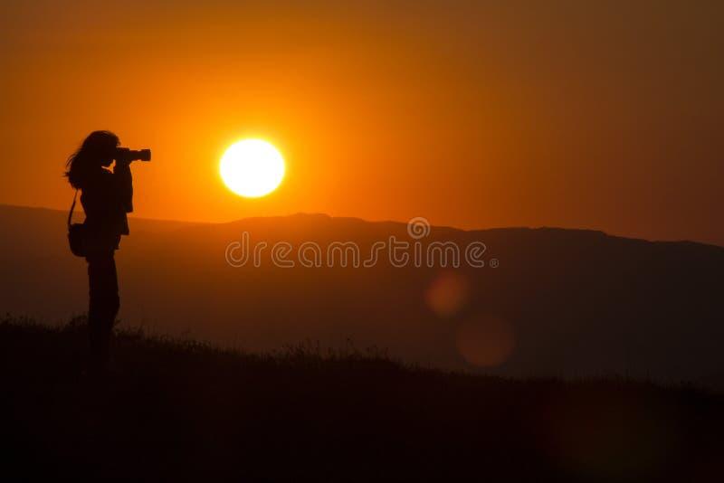 Kontur av fotografen p? solnedg?ngen arkivbild