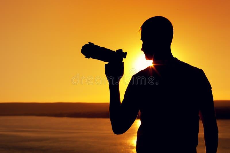 Kontur av fotooperatören nära havet på solnedgången royaltyfri foto