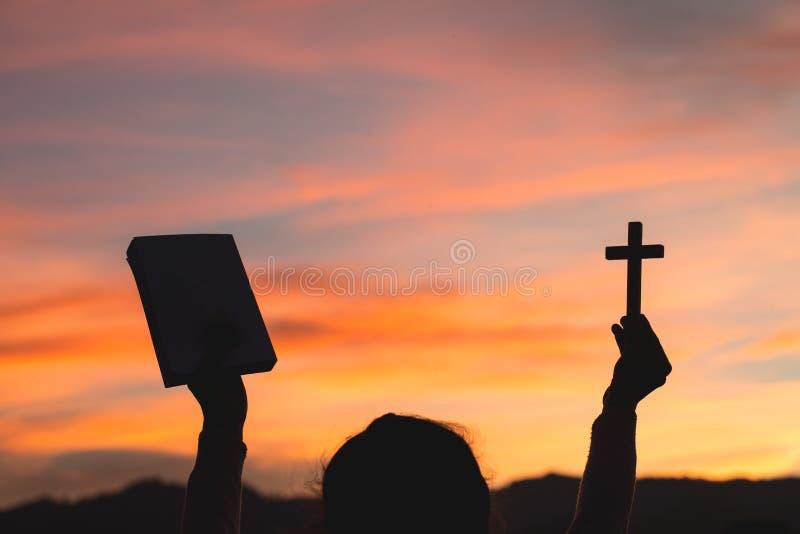 Kontur av händer för ung kvinna som rymmer den heliga bibeln och elevatorn av det kristna korset, religionsymbolet i ljus och lan royaltyfria foton