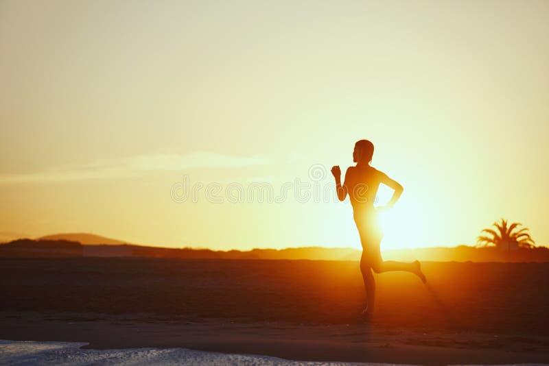 Kontur av idrotts- flickaspring längs stranden på fantastisk orange solnedgångbakgrund royaltyfria bilder