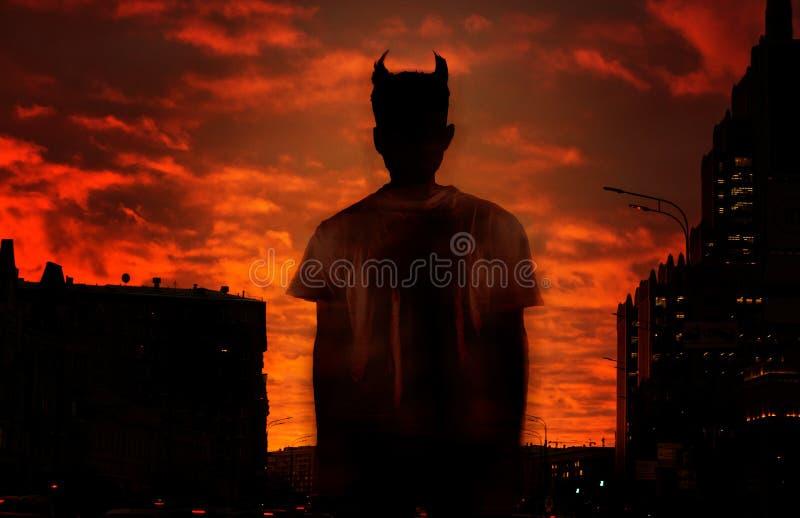 Kontur av jäkeln på bakgrunden av den röda blodiga himlen royaltyfri fotografi