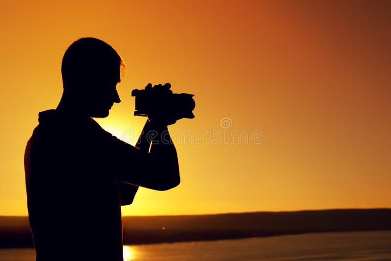 Kontur av kameramannen nära havet på solnedgången arkivfoton