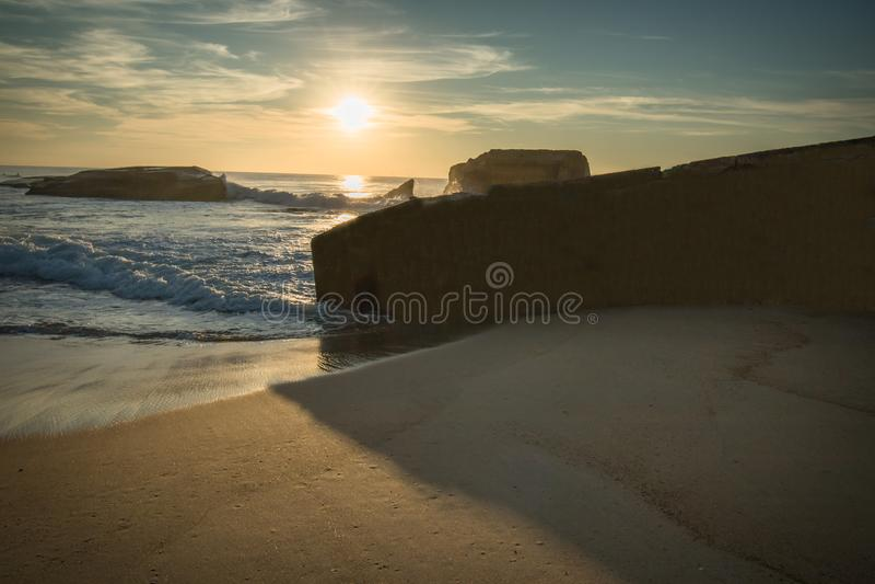 Kontur av krigblockhuset på scenisk härlig seascape för sandig strand med vågor på Atlantic Ocean i blå guld- solnedgånghimmel i  royaltyfri foto
