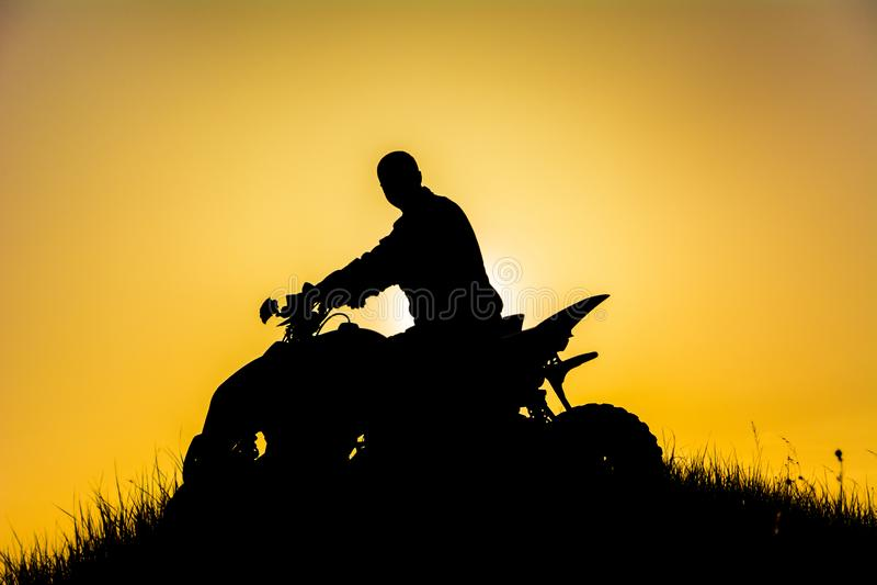 Kontur av kvadratcykelchauffören på berget royaltyfria foton