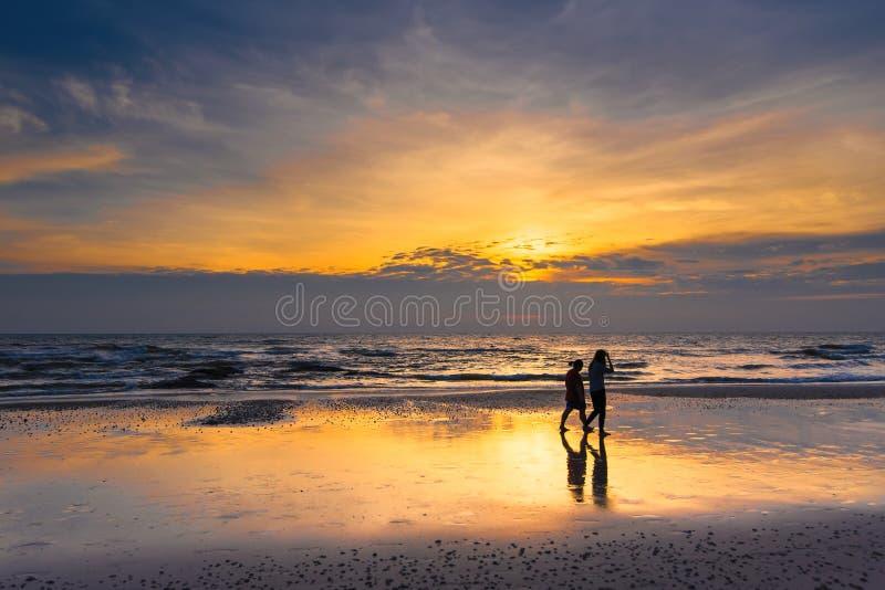 Kontur av kvinna som två går på strandsoluppgången i morgonen arkivbild