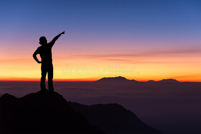 Kontur av kvinnaanseendet på överkanten av berget och att peka arkivfoton