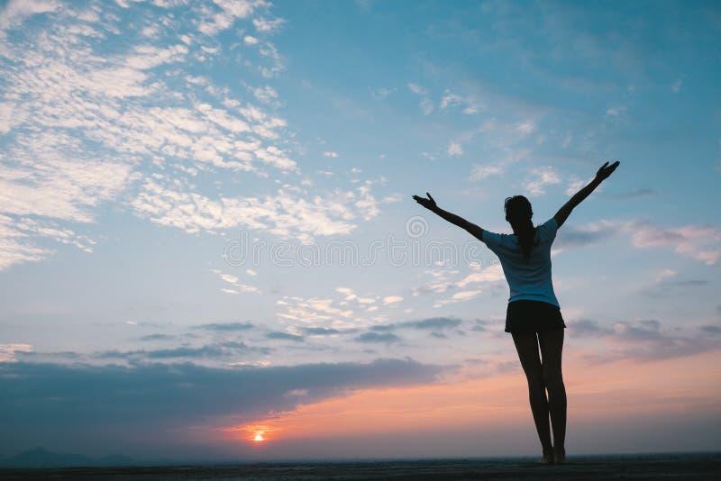 Kontur av kvinnafrihetskänsla i solnedgång royaltyfria foton