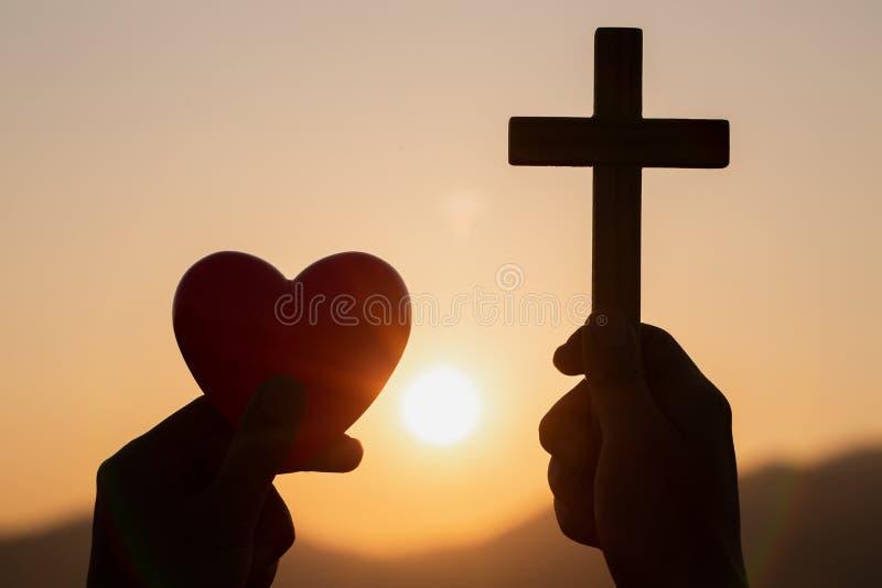 Kontur av kvinnahänder som ber med korset och rymmer en röd hjärtaboll i natursoluppgångbakgrund, kors, symbol av arkivbild