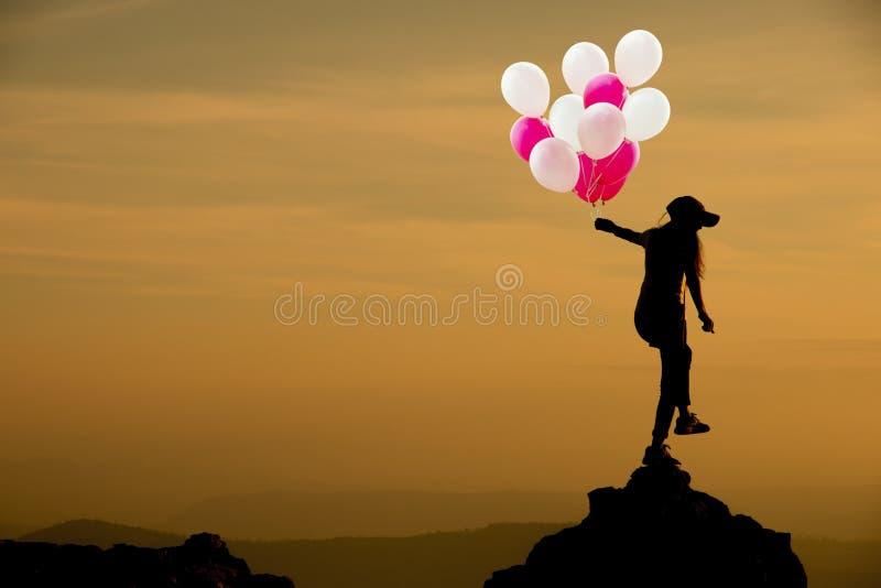 Kontur av kvinnainnehavballongen på klippan och bergen med solnedgång i aftonen royaltyfri illustrationer