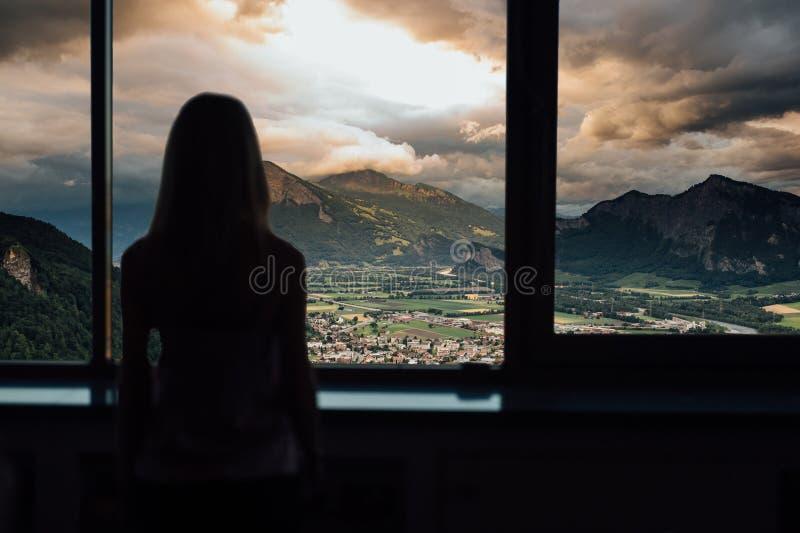 Kontur av kvinnan i solsken på fönstret med sikt på solnedgång i berg arkivfoton