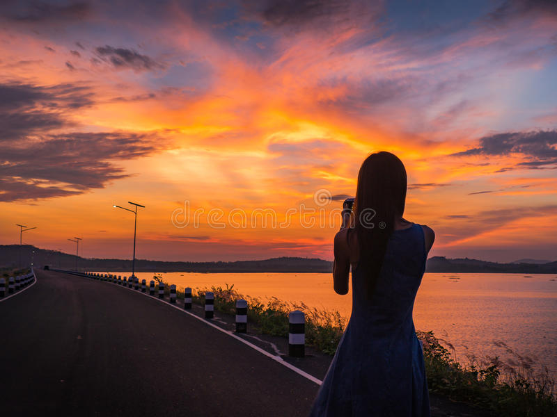 Kontur av kvinnan på sjön, soluppgångbakgrund arkivbild